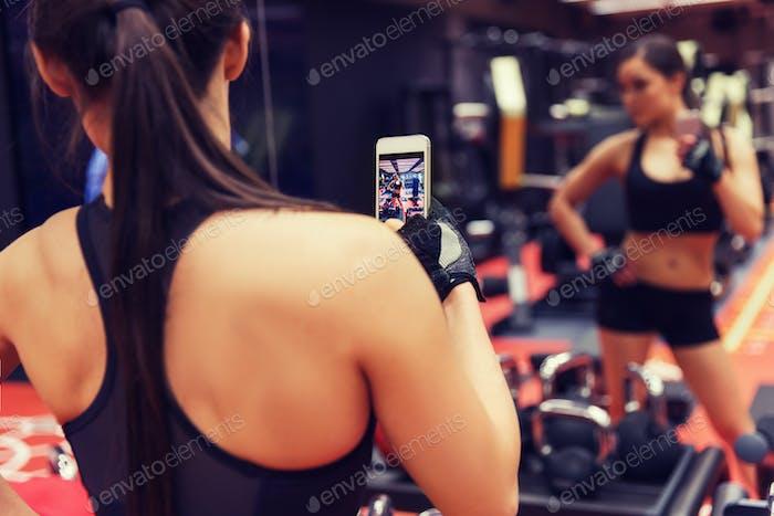 Mujer con smartphone Encantador espejo selfie en gimnasio