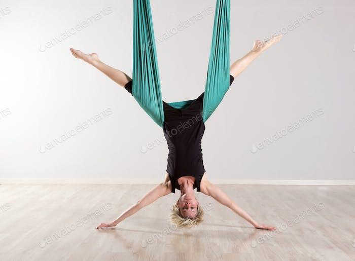Single upside down woman doing aerial yoga splits