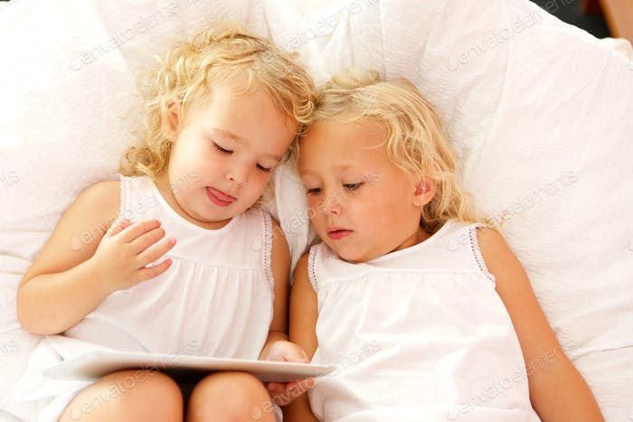 Innocent little sisters using digital tablet on bed