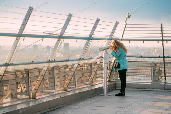 Minsk, Belarus. Young Woman Looking At Coin Operated Telescope F