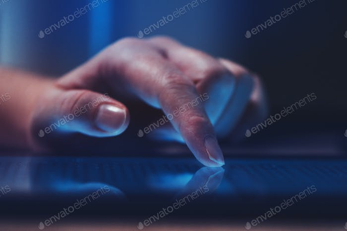 Extreme close up of female finger using digital tablet computer