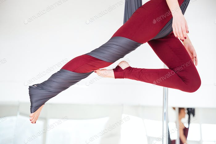 Young woman legs in leggins practicing aerial yoga at studio