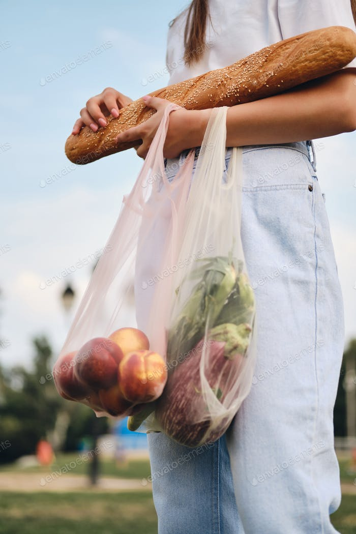 Close up woman standing with baguette bread, peaches and vegetables in eco bags in city park