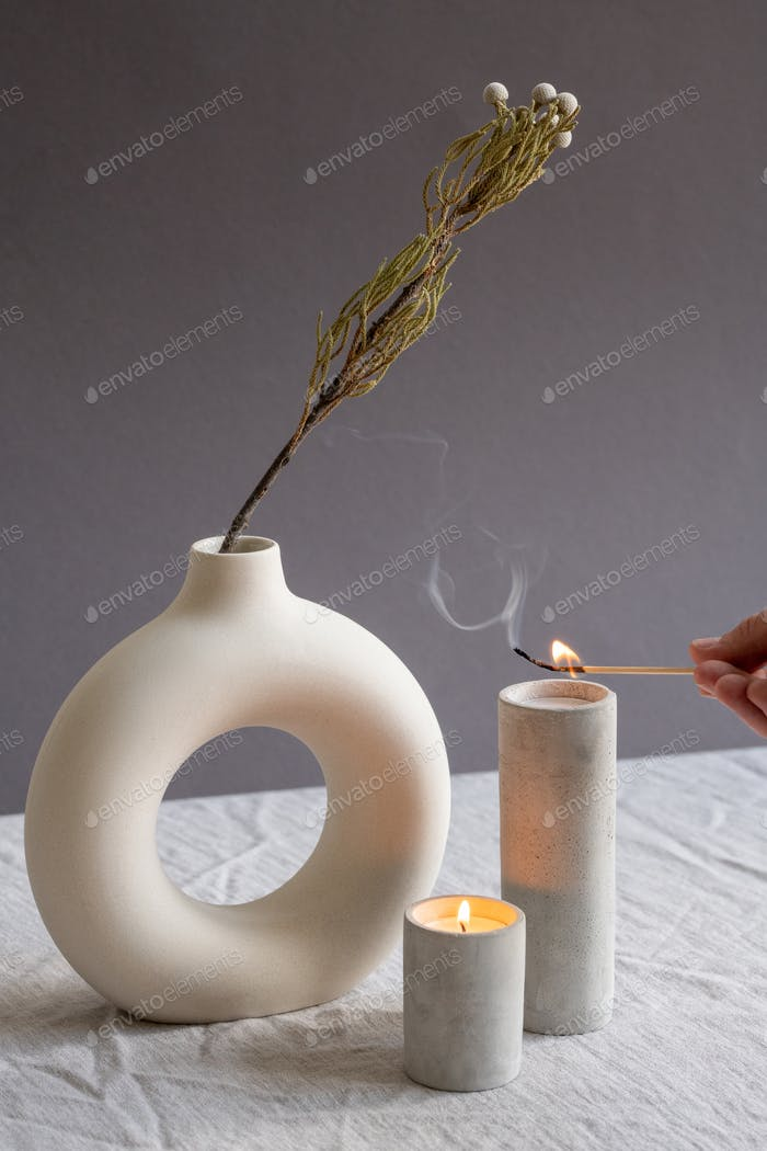 Hands of young woman holding burning match over one of two aromatic candles