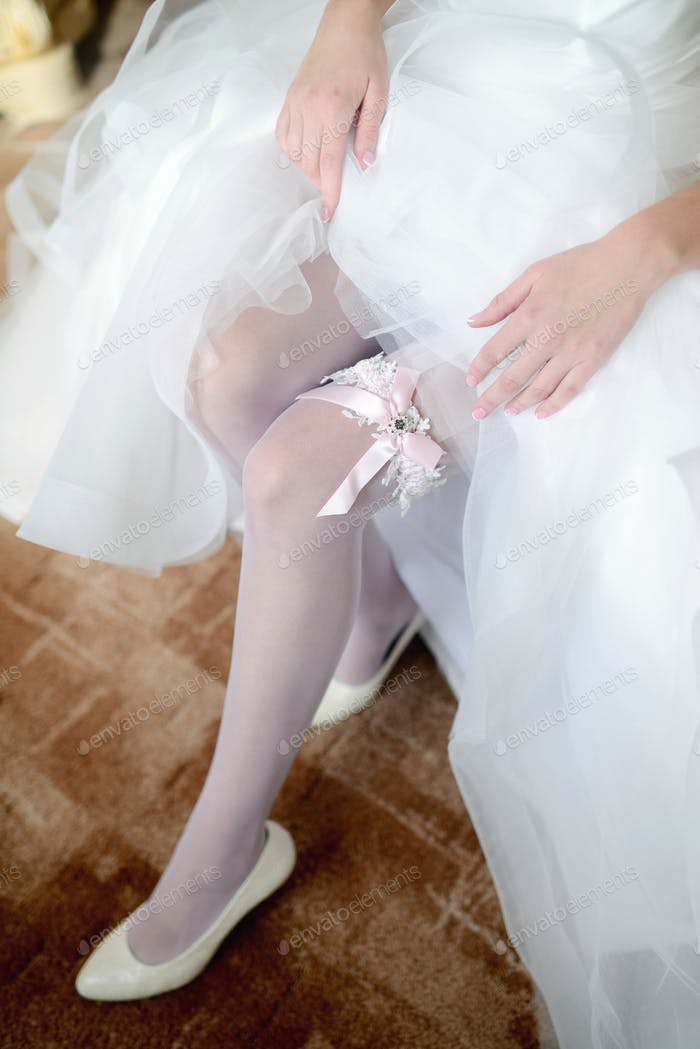 Beauty bride in dressing gown is wearing bridal garter indoors