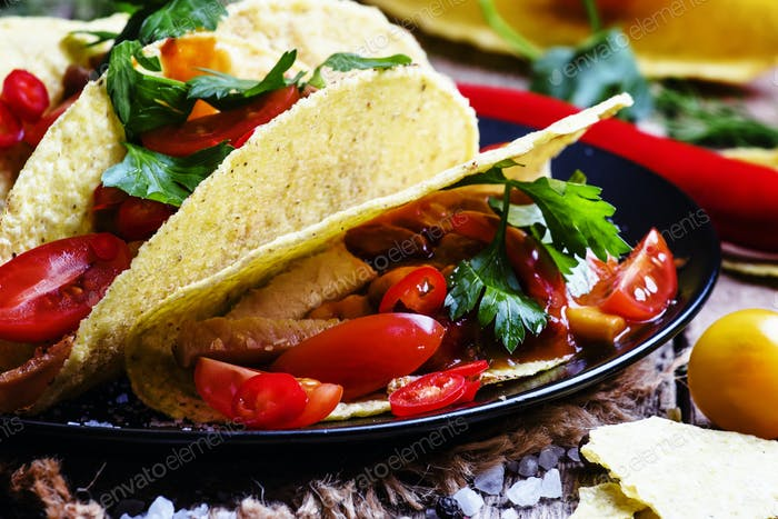 Mexican tacos stuffed with meat, beans, tomatoes and chili peppers