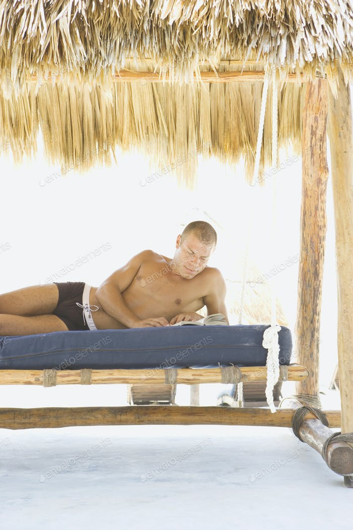 Bare chested man reading on a mattress at the beach