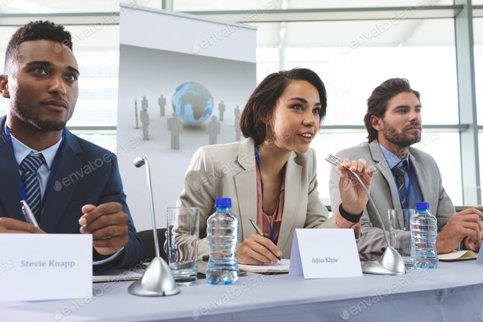 Front view of young mixed race business people sitting at table in seminar