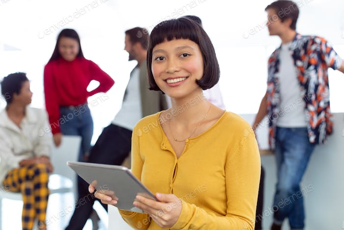 Front view of happy young Asian businesswoman with digital tablet standing in a modern office