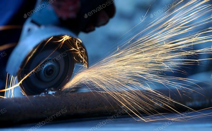 Arbeiter schneiden Metall mit Schleifer