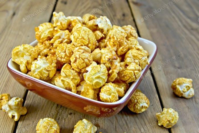 Popcorn caramel on board in clay bowl