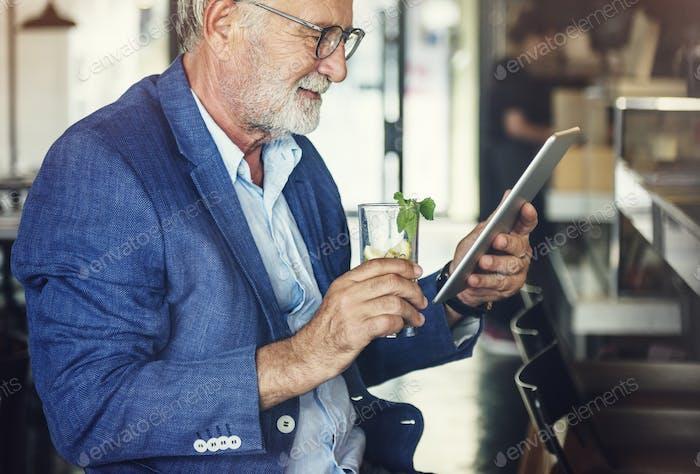 Old Man Holding Tablet Cocktail Concept