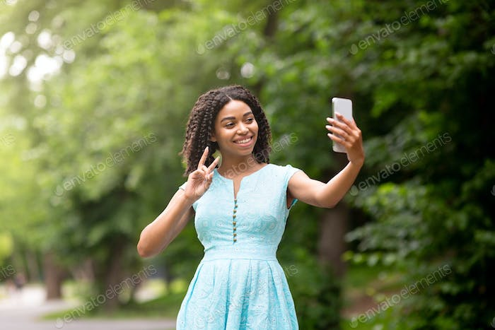 Beautiful African American girl taking selfie or communicating online on cellphone at park