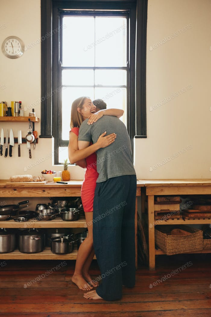 Cheerful young couple embracing each other in kitchen