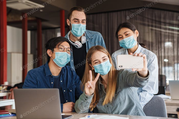 Photo of cheerful students in medical masks taking selfie on cellphone