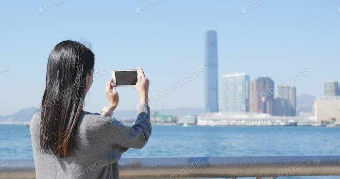 Woman taking photo in Victoria harbor