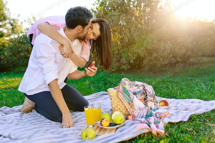 Happy couple having a picnic in park on a sunny day, kissing and hugging