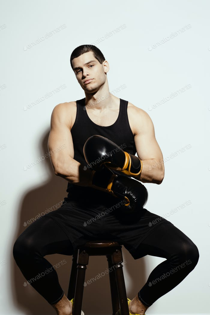Boxer putting on his boxing gloves while resting on the chair
