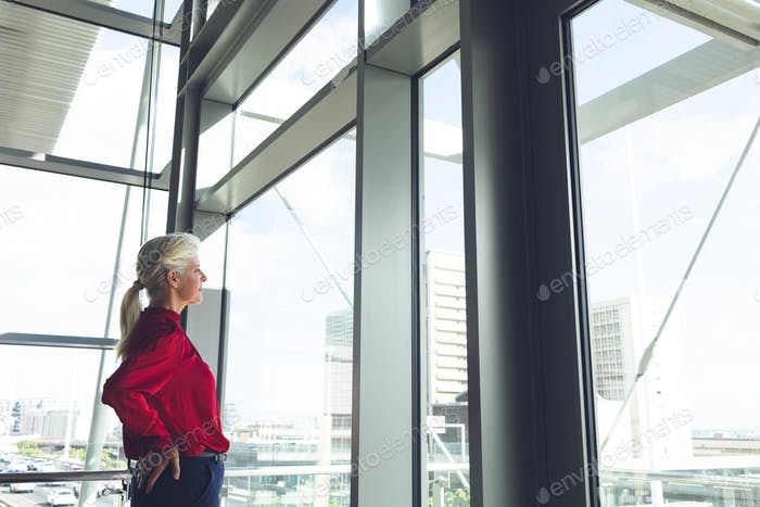 Senior businesswoman with hands on hip looking through window in office