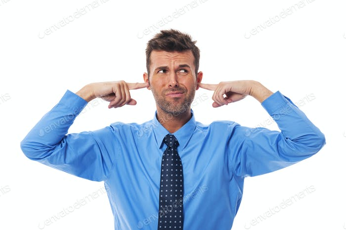 Disgust business man with fingers in ears