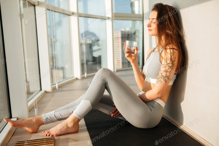 Pensive lady in sporty top and leggings sitting on yoga mat holding glass of water next to windows