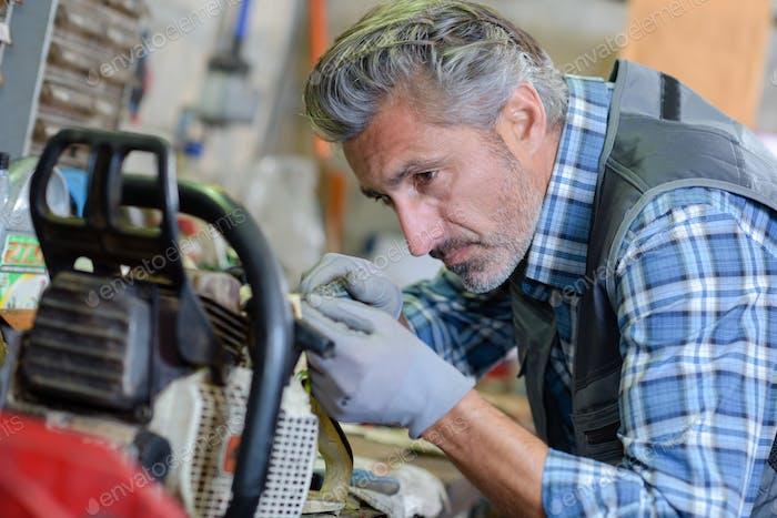 Mechanic working on gardening equipment
