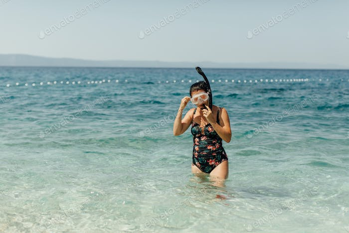 Woman getting ready to snorkel in sea.