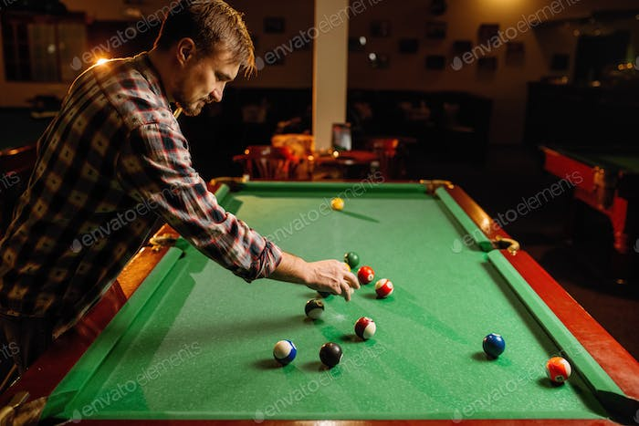 Male billiard player places balls, poolroom