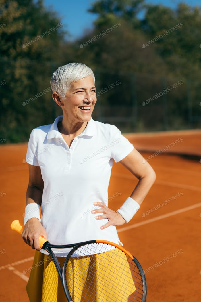 Schöne Reife Frau auf dem Tennisplatz