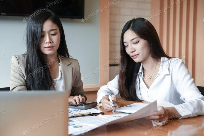 Two young women are discussing work in the conference room.