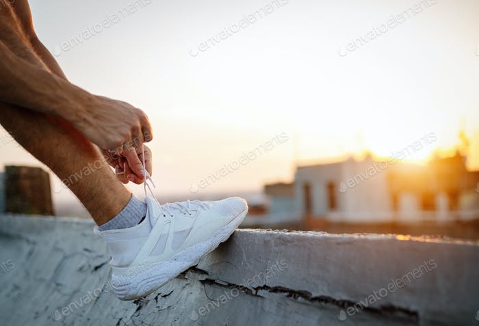Closeup portrait of a man tying shoelaces outdoor