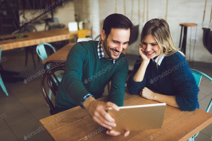 Young attractive couple having fun with tablet in cafe
