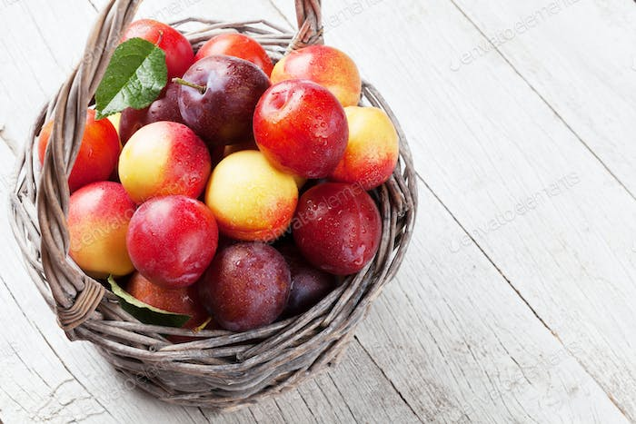 Fresh ripe peaches and plums in basket