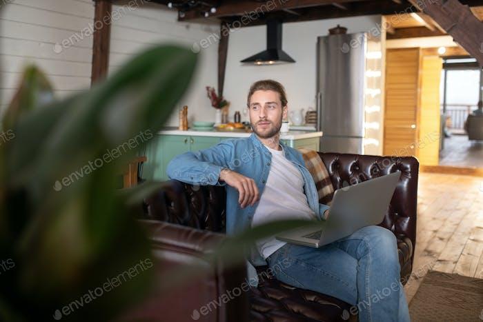 Nachdenklicher Mann, der von zu Hause aus mit einem Computer arbeitet