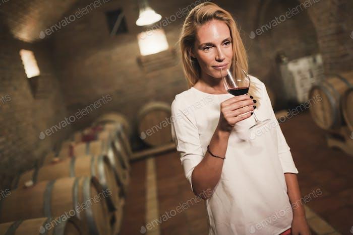 Beautiful woman oenologist tasting wine