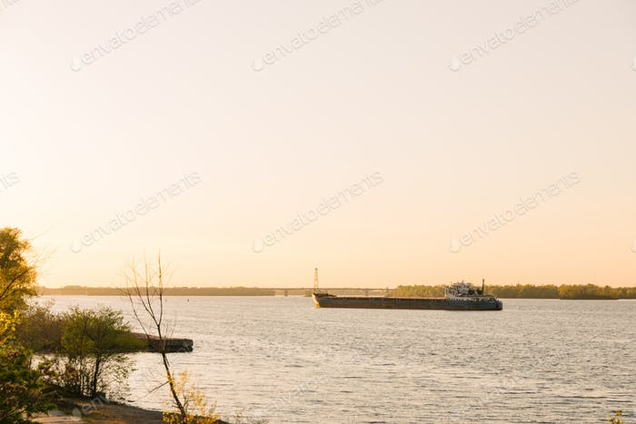 An empty moored barge is waiting on the sunset to the bulk carrier.