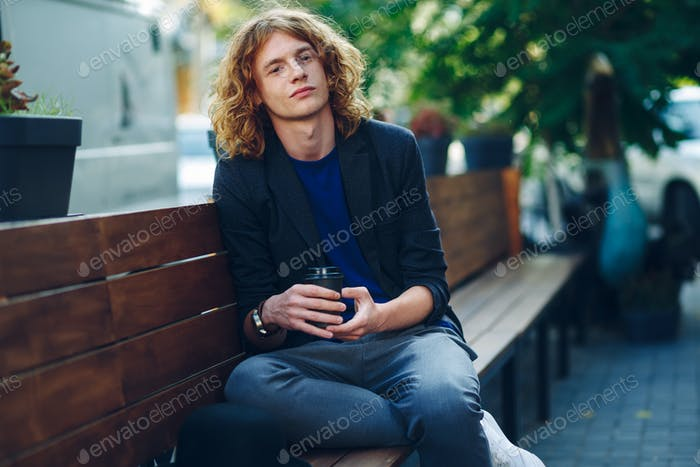 Handsome man sitting on bench with coffe to go