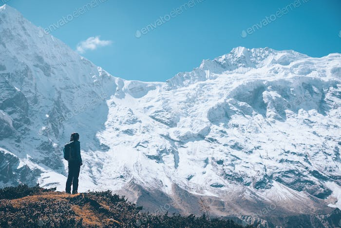 Woman on the mountain trail and looking on snow covered rocks