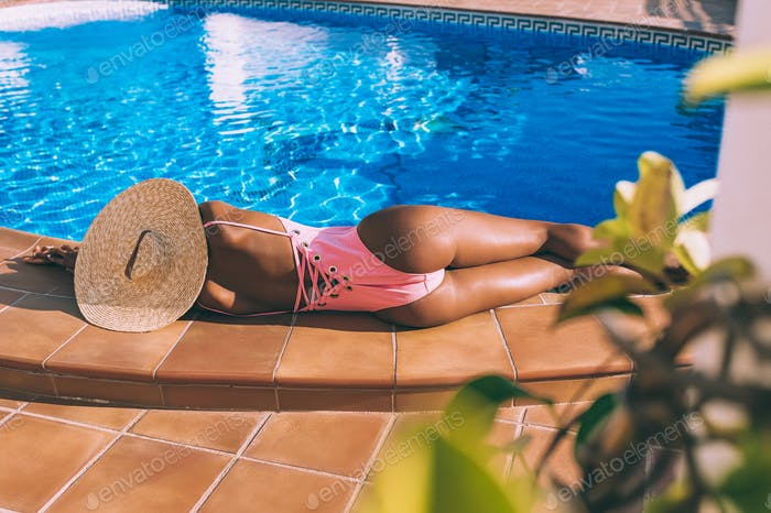 Black woman lying down in a swimming pool side