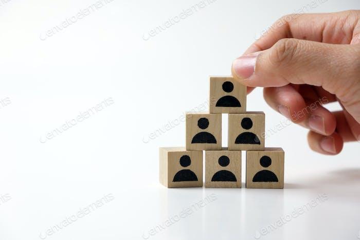 Businessman stacking wooden team blocks