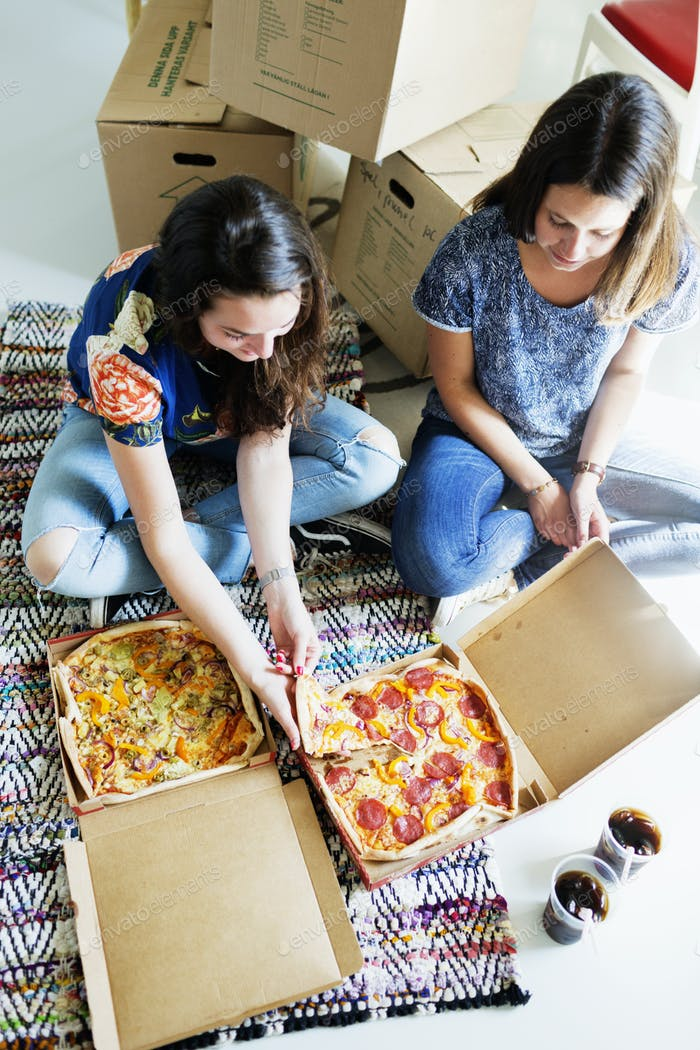 High angle view of friends eating pizza while sitting against boxes