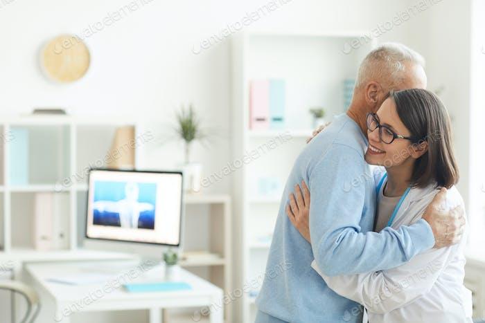 Lächelnde Ärztin Umarmung Senior Man