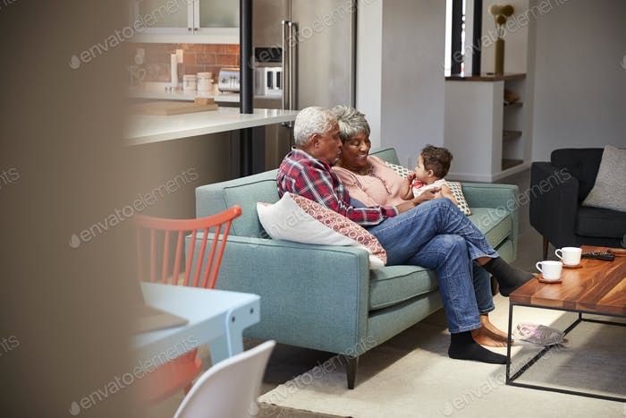 Grandparents Sitting On Sofa With Baby Granddaughter At Home