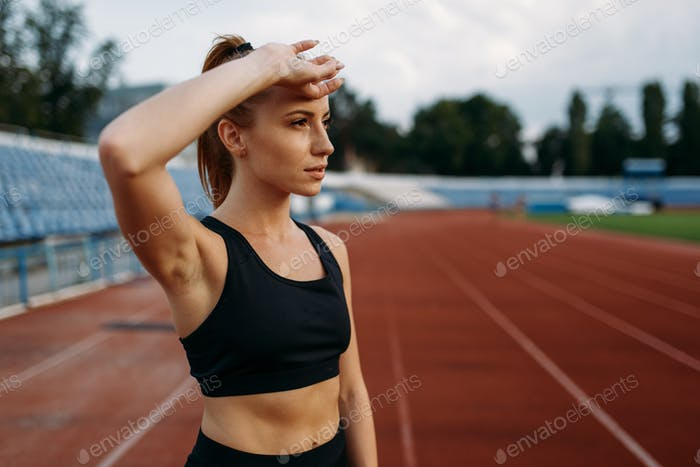 Tired female runner, training on stadium