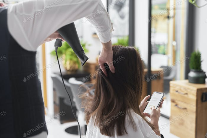 Close up of hairdresser using hair dryer