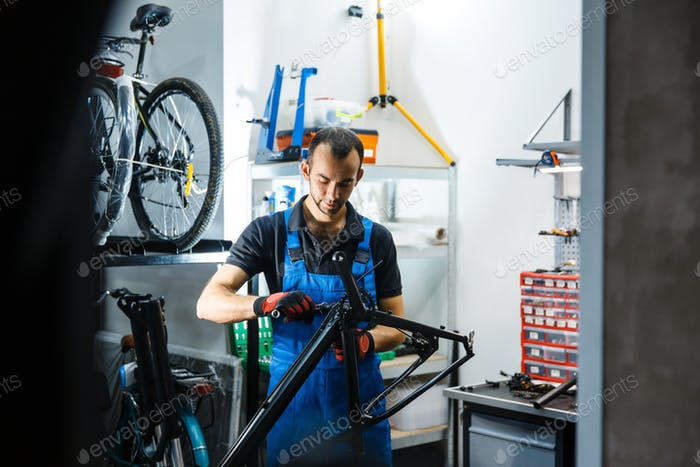 Bicycle repair in workshop, man fixing crank