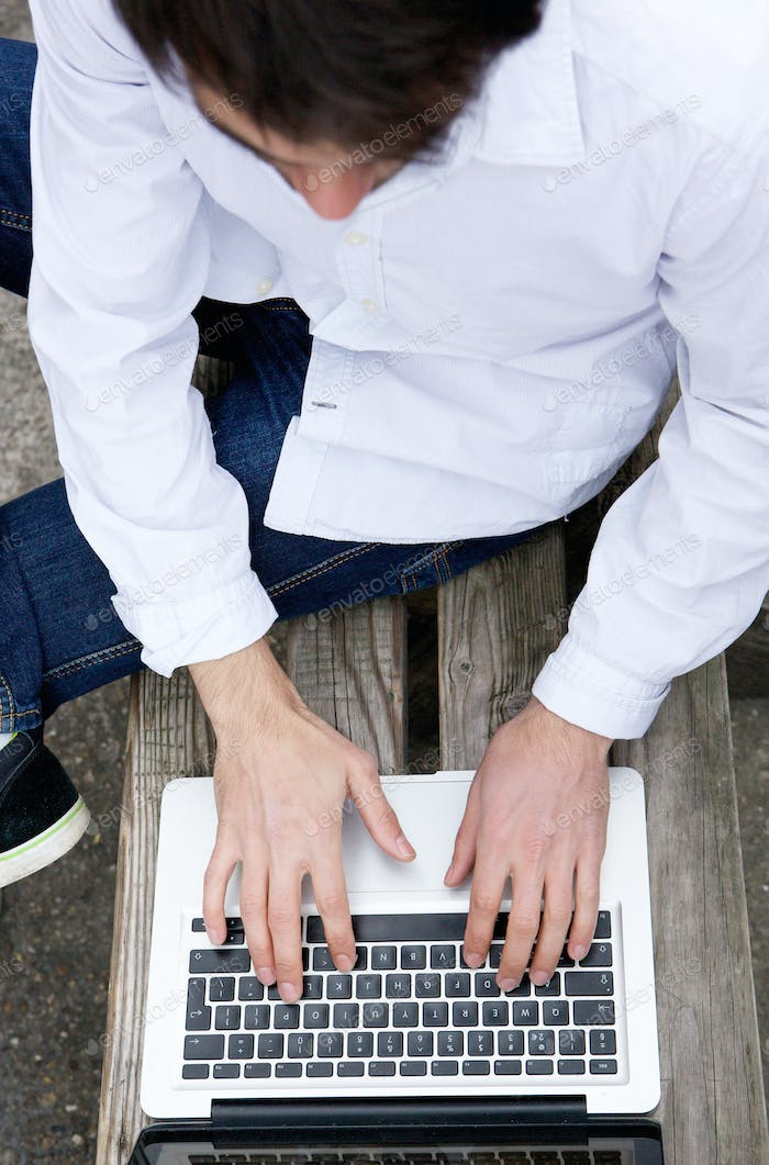 Top view of a young man typing on laptop