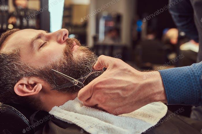 Professionelle Friseur Modellierung Bart mit Schere und Kamm im Friseur.