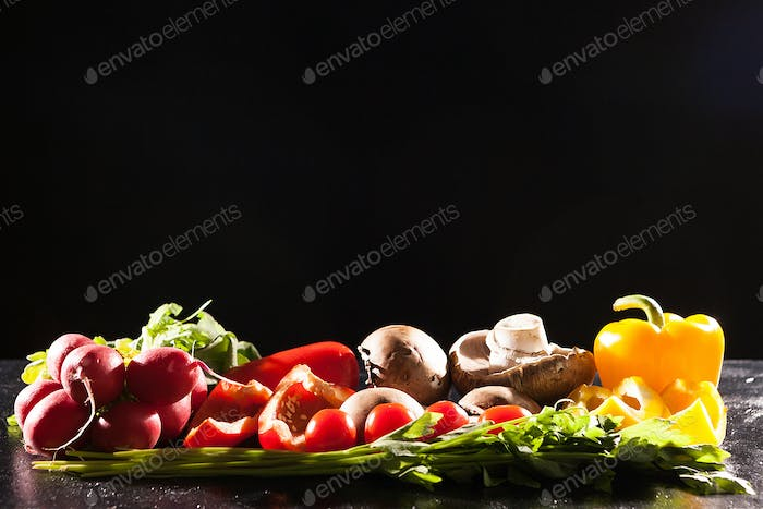 Different type of organic healthy vegetables on dark wooden back