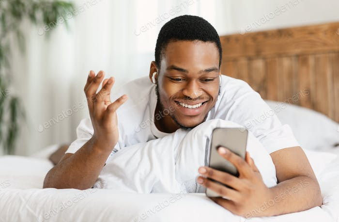 Happy Black Man Making Video Call Lying In Bed Indoors